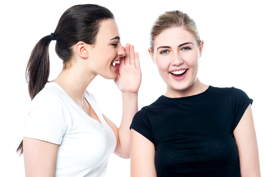 Beautiful smiling girls sharing a secret