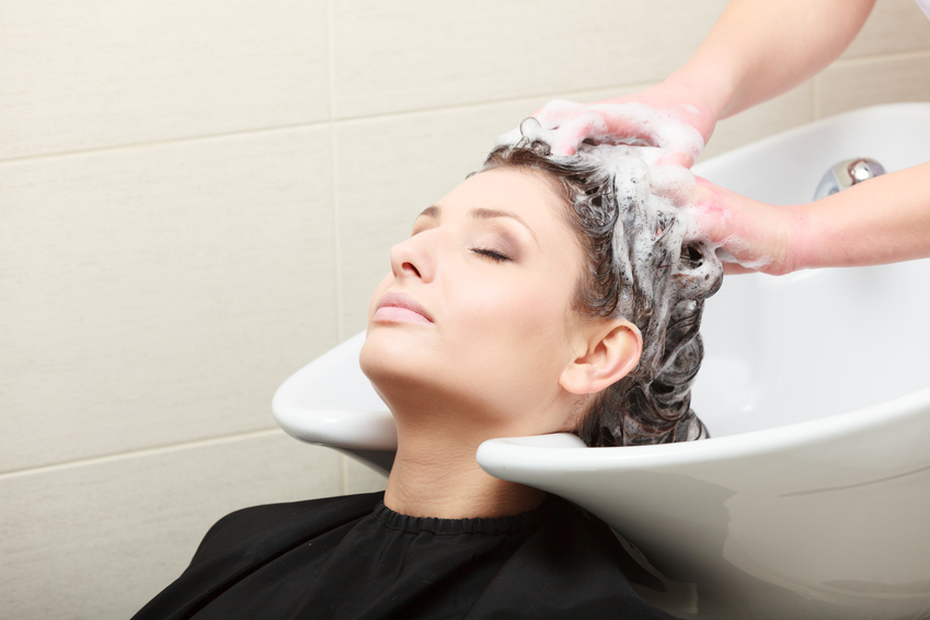 Hairdressing salon. Hairstylist washing hair woman client.