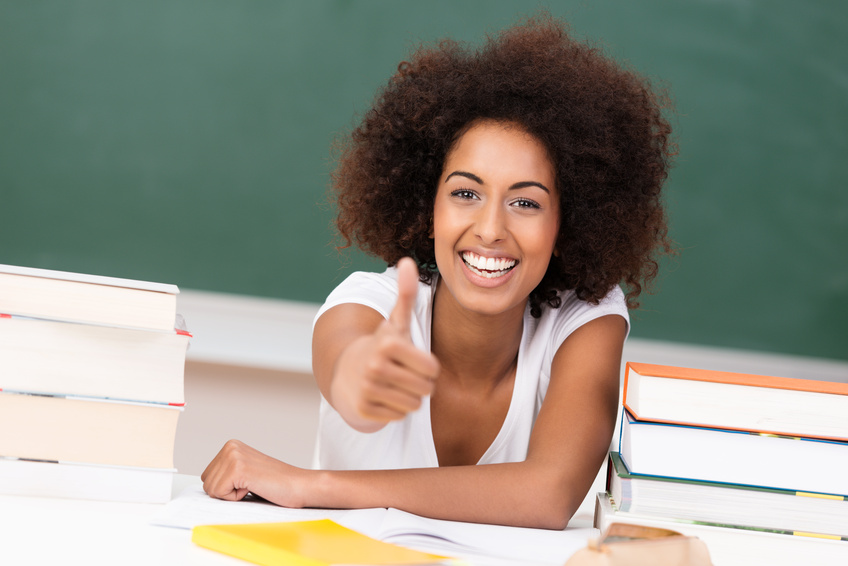 lachende studentin zeigt daumen hoch