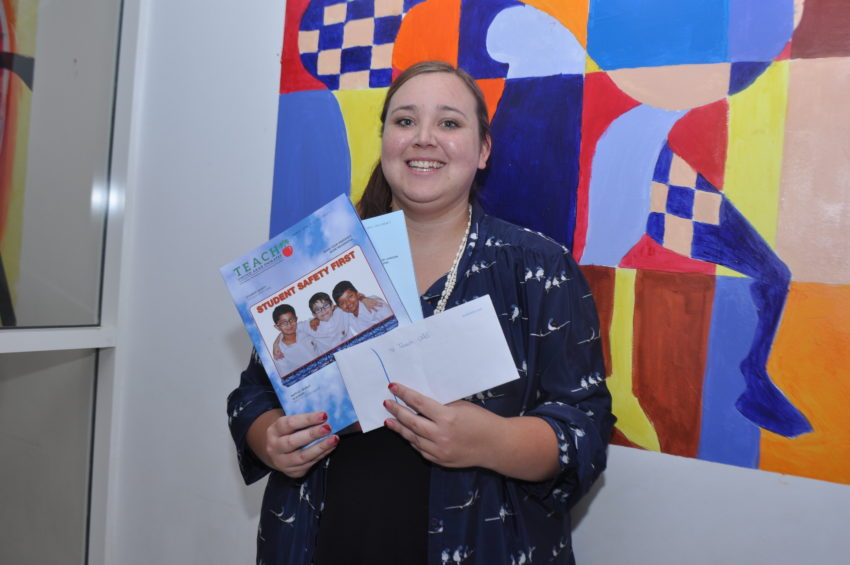 Elsi smiles happily with her prize and a copy of the January -February issue of Teach UAE Magazine.