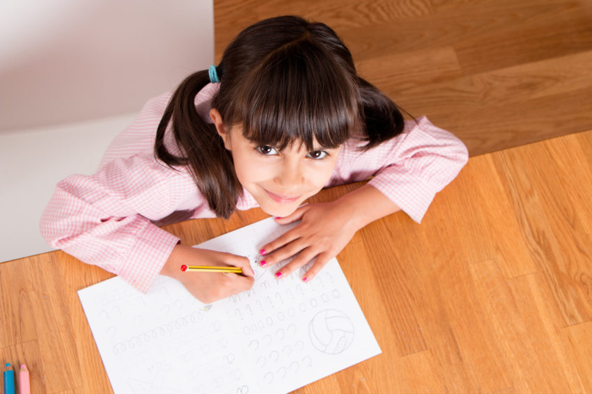 Happy little girl in uniform doing calligraphy exercises. Top view