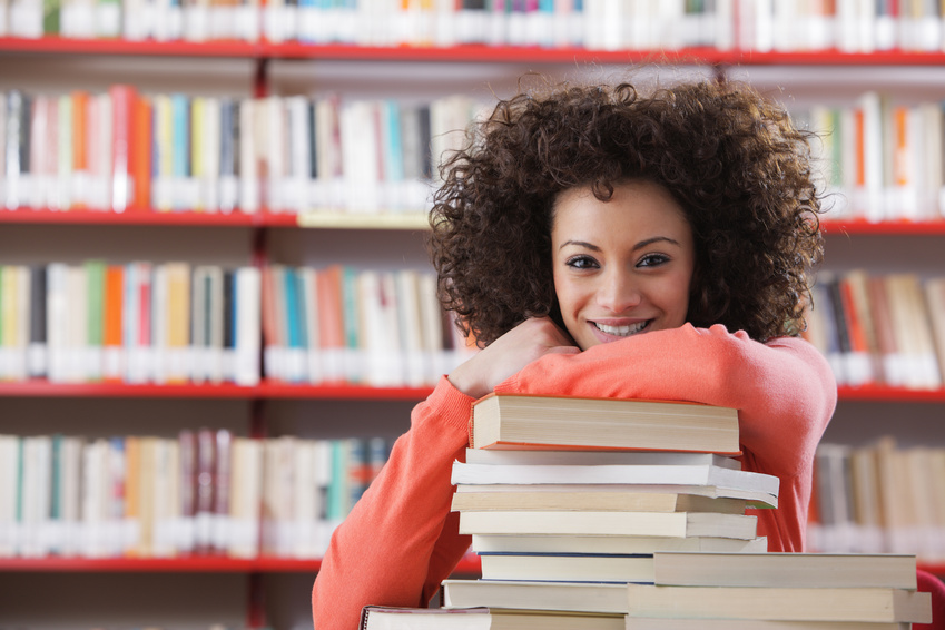 Portrait of cheerful female student in library