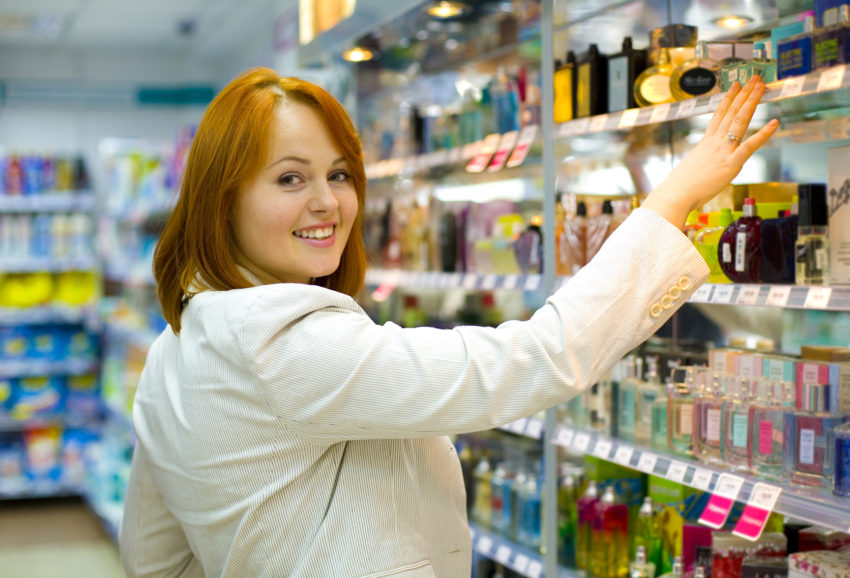 Young woman in shop of cosmetics and perfumery chooses spirits