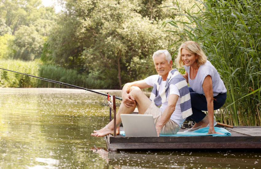 Portrait of senior couple sitting at the lake and fishing while surfing on internet.